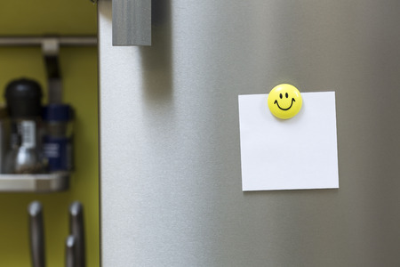 Nota de papel en blanco con el imán que cuelga en la puerta del refrigerador Foto de archivo