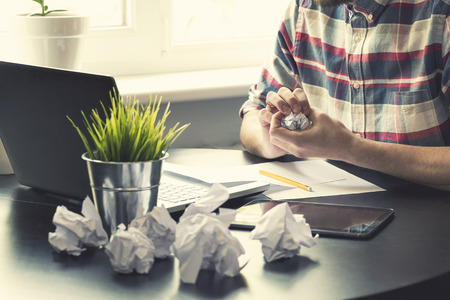 office workplace with many crumpled paper balls on the table
