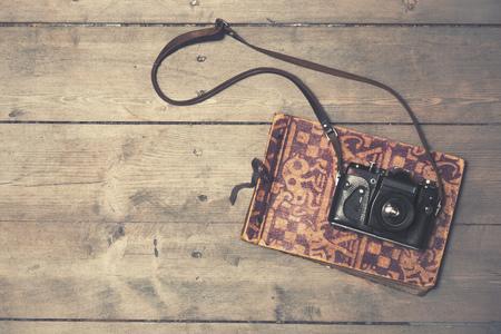 vintage photo: retro camera with vintage photo album on wooden background Stock Photo