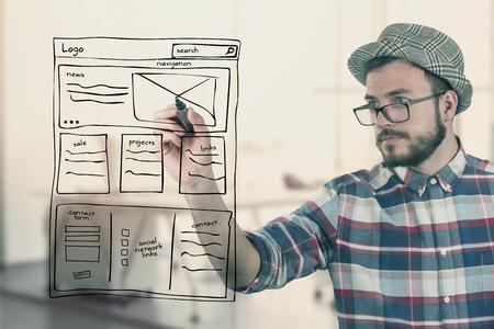 web designer drawing website development wireframe at office