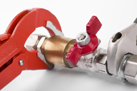 plumbing accessories: closeup of plumbing valve connection and pipe wrench