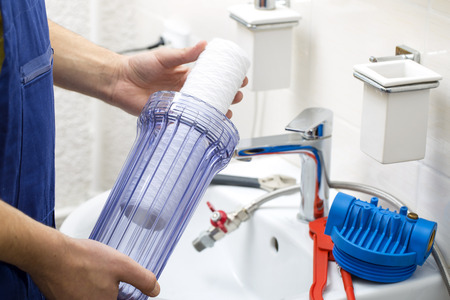 plumber installing new water filtration system Foto de archivo