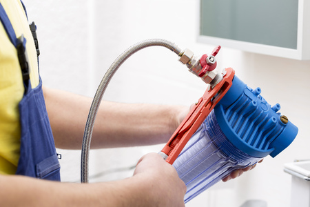 filtration: plumber installing new water filter in bathroom