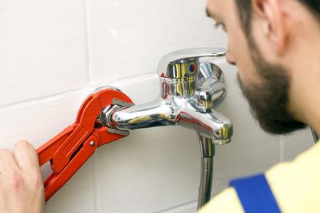 installing: plumber installing water tap in bathroom Stock Photo