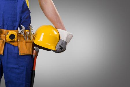 hombre con sombrero: trabajador de la construcción que sostiene el casco en fondo gris con el espacio de la copia Foto de archivo