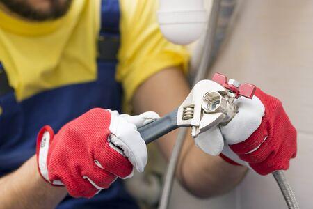 screwing: plumber screwing plumbing fittings in bathroom