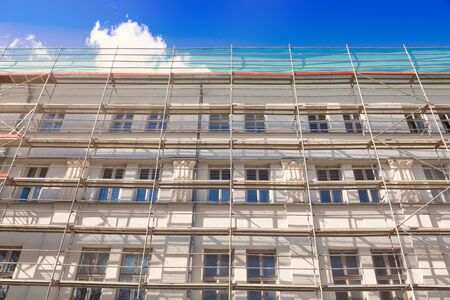 renovate old building facade: house exterior with scaffold - old town building facade restoration