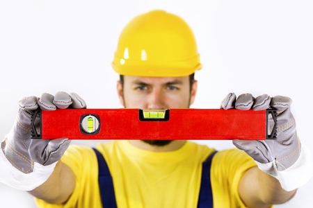 quality control - construction worker with spirit level Stock Photo