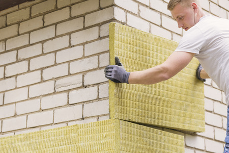 Bauarbeiter mit Mineralwolle isolierende Hausfassade Standard-Bild - 57525722
