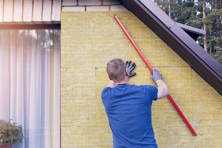 rockwool: construction worker checks the level of insulated house wall