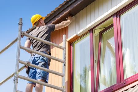 pintor: trabajador de la construcción en la pintura de andamios de fachada casa de madera