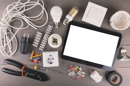 blank digital tablet with electrical tools and equipment on wooden table