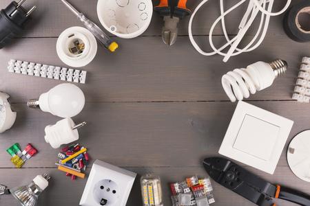 strom: Draufsicht auf elektrische Werkzeuge und Geräte auf Holztisch