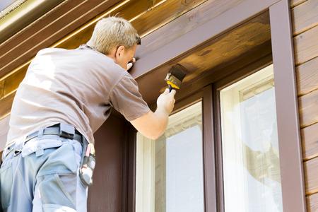Człowiek z pędzlem do malowania drewnianych domu Reklama publiczna