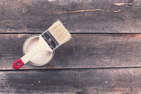 paint tool: paint can with paintbrush on old wooden background Stock Photo