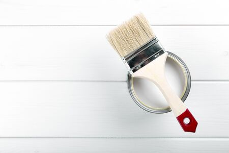 paint tool: paint can with paintbrush on white wooden background with copyspace Stock Photo