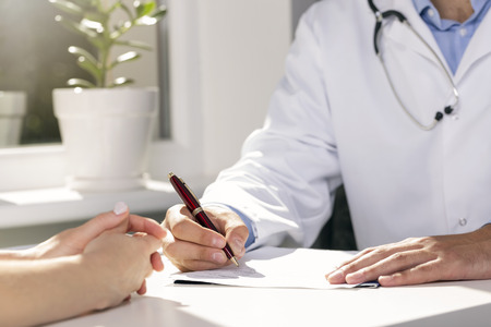 doctor consultation: medical consultation - doctor and patient sitting by the table