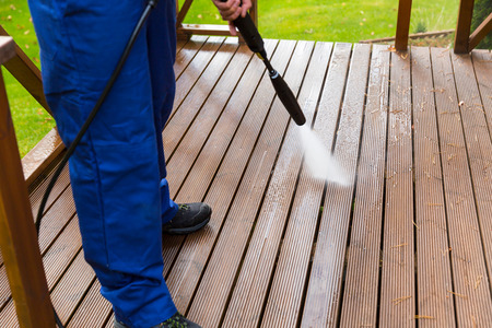 cleaning wooden terrace with high pressure washer Stockfoto
