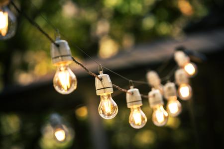 Chaîne de lumières extérieures suspendus sur une ligne dans la cour Banque d'images - 65571404