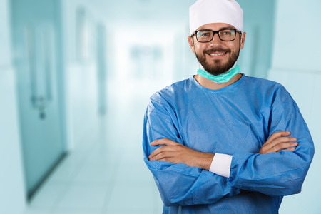 protective: happy smiling doctor surgeon standing in the hospital hallway