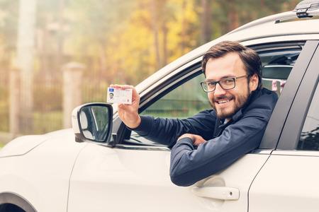chofer: hombre sentado en el coche y mostrando su licencia de conducir