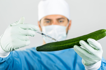 genetically: genetically modified food - scientist make injection in cucumber with syringe Stock Photo
