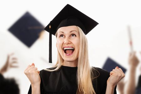 young happy college graduate wearing cap and gown Stock Photo