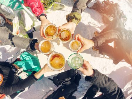 winter break: winter holidays - group of friends drinking beer on break at ski resort