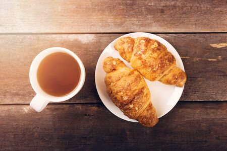 breakfast cup: breakfast croissant with cup of tea on wooden table Stock Photo