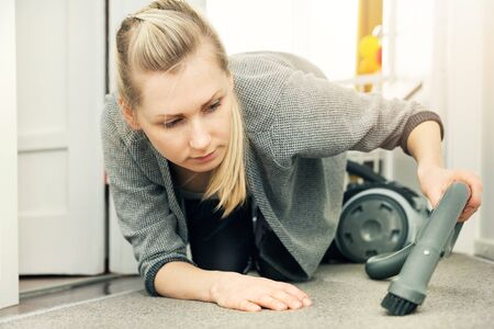 pedantic: pedantic woman cleaning house with vacuum cleaner
