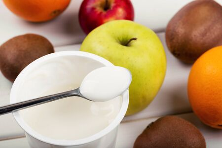 spoon with yogurt and fruits on white wooden table