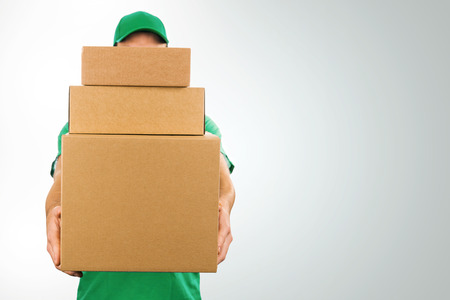 delivery man holding pile of cardboard boxes in front with copy space Stockfoto