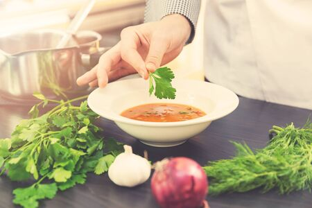 chef decorating soup with herbs in kitchen