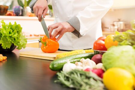 domestic kitchen: cook preparing vegetable salad in domestic kitchen