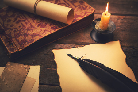 writing desk: vintage feather with paper and old book on table in light of candle