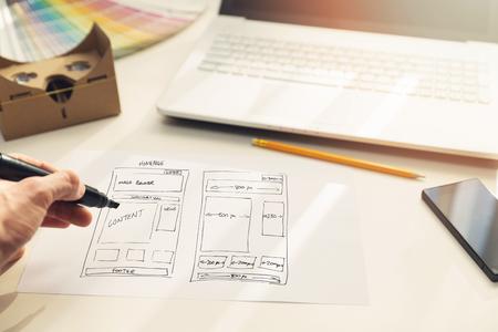 디자이너 사무실에서 종이에 웹 사이트 개발 와이어 프레임을 그리기 스톡 콘텐츠
