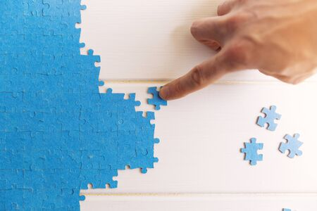 challenge and strategy concept hand connecting jigsaw puzzle