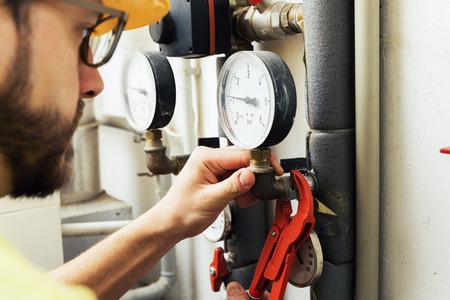 service engineer: plumber installing pressure meter for house heating system