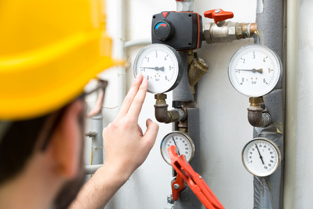 maintenance - technician checking pressure meters for house heating system Фото со стока