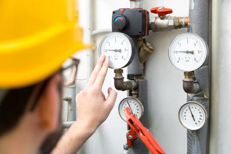 mantenimiento - técnico que comprueba los medidores de presión para el sistema de calefacción de la casa Foto de archivo