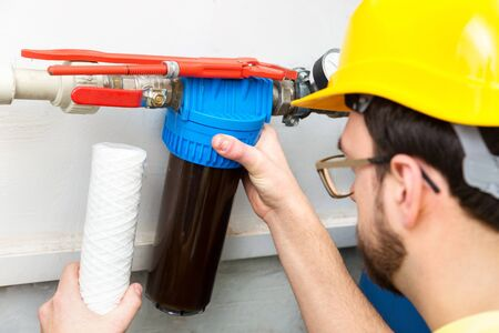 water filtration - plumber changing dirty water filter Banque d'images