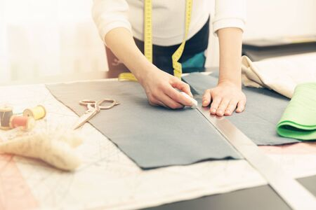 tailored: woman tailor working. marking the fabric with chalk Stock Photo