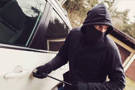 car theft - thief trying to break into the vehicle