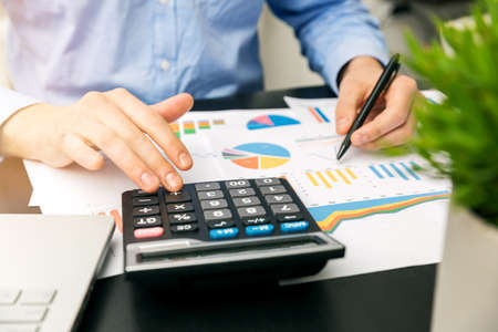 financial reports: businessman analyzing financial graphs and reports in office Stock Photo