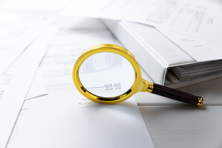 audit concept - magnifying glass and business documents