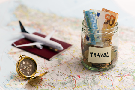 travel concept - money savings, compass and passport on a map