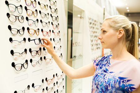 eye care - young woman choosing new glasses in optician store photo