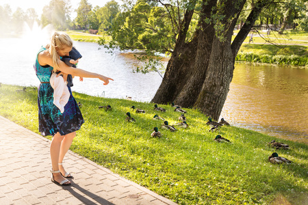 mother showing ducks to her baby near the park pond photo