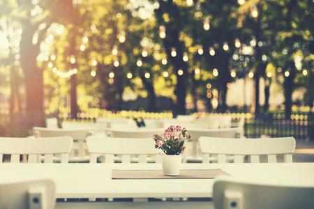 Romantisches Restaurant im Freien im Park mit Lichterketten bei Sonnenuntergang Standard-Bild - 80863707