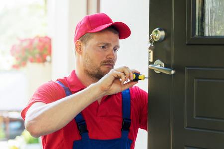 Cerrajero, rojo, uniforme, instalación, nuevo, casa, puerta, cerradura Foto de archivo